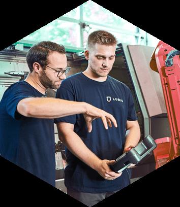 Dekoratives Element: Zwei Arbeiter an Roboter-Arm